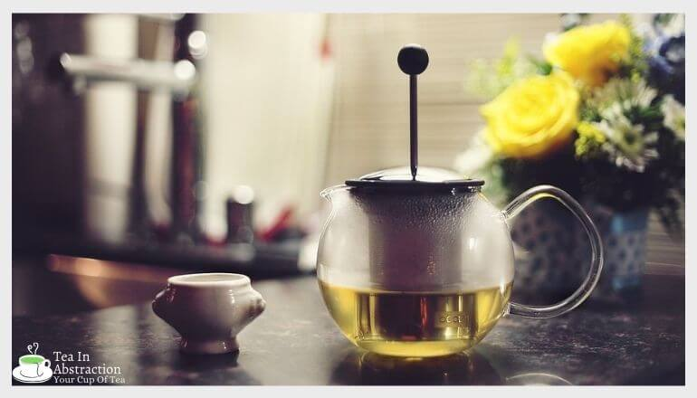 green tea in a tea press kettle next to a tea cup