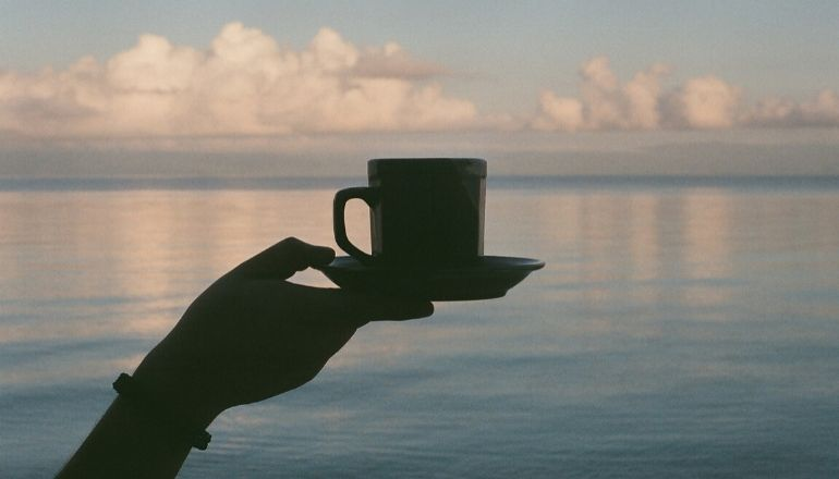 woman holding cup of anise tea up to horizon