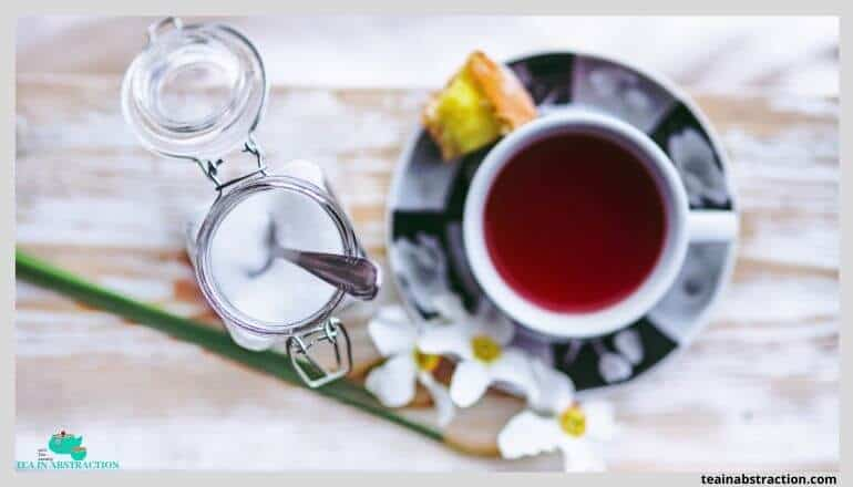 red hibiscus tea in a white cup on a saucer sitting oon a table next to an open jar of sugar with a spoon in it. flowers adorn the image as well