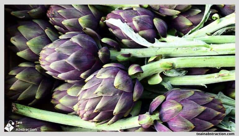 purple artichokes with green stalks in a pile
