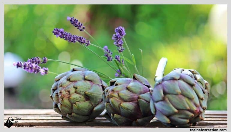3 green and purple artichoke sitting on a wood table with lavender flowers arranged around them
