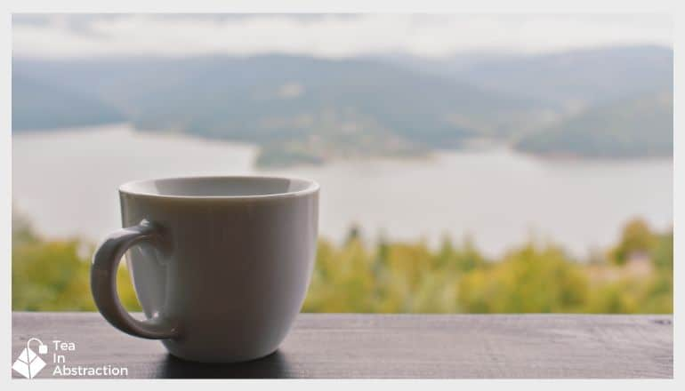 cup of tea on a table with a lake and mountains in the background