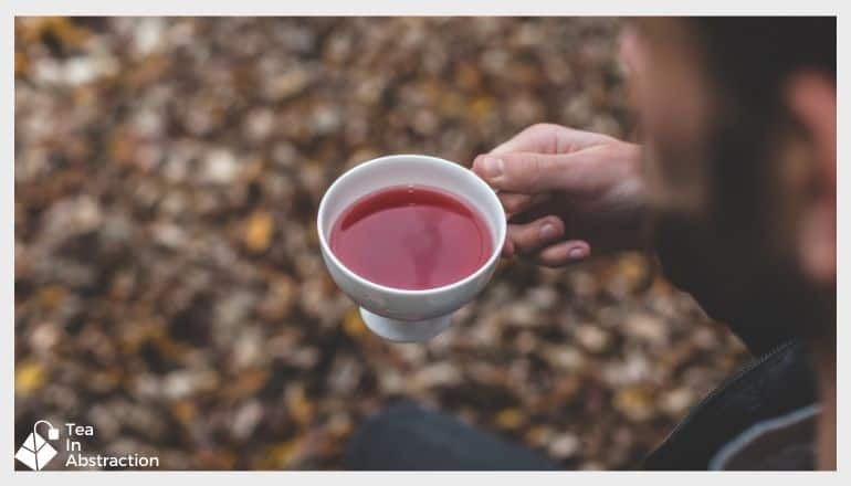 man drinking a cup of red tea