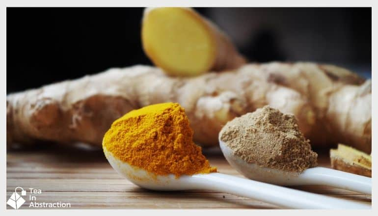 powdered ginger and turmeric root heaped on spoons and resting in front of ginger root