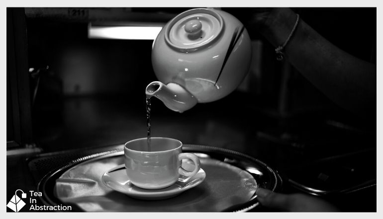 black and white image of kettle pouring water into a tea cup