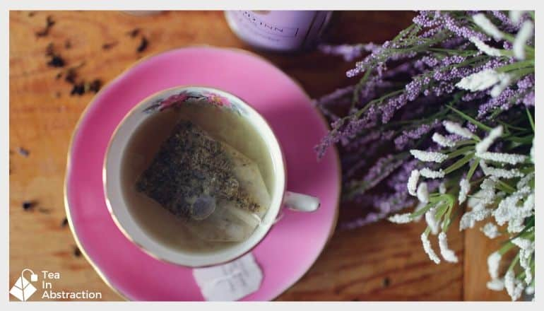 Cup of lavender tea with fresh lavender next to it