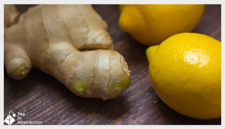 fresh ginger root and 2 uncut lemons arranged on a wood table