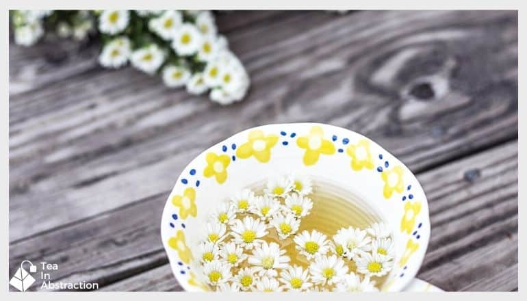 cup of chamomile tea with fresh Chamomile flowers nearby