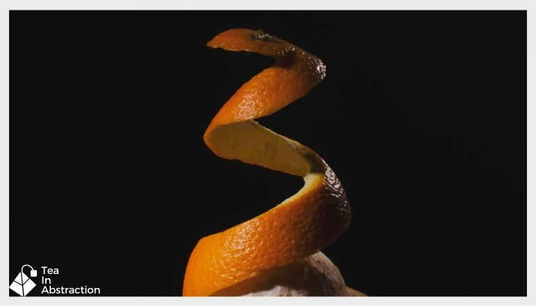orange peel being removed from and orange against a black background