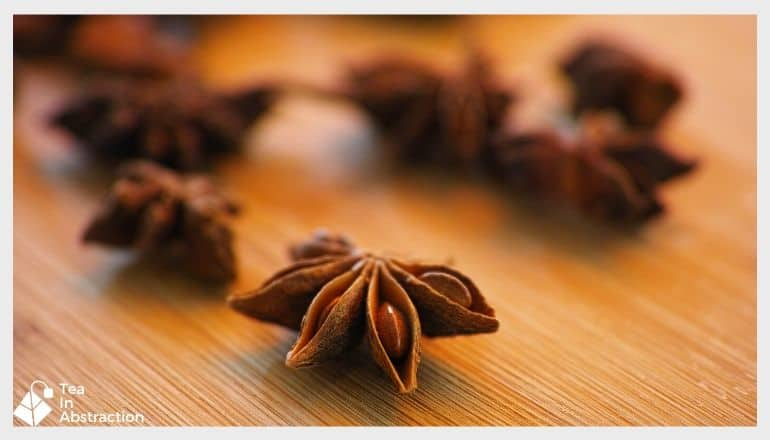 star anise pods scattered over a wooden table