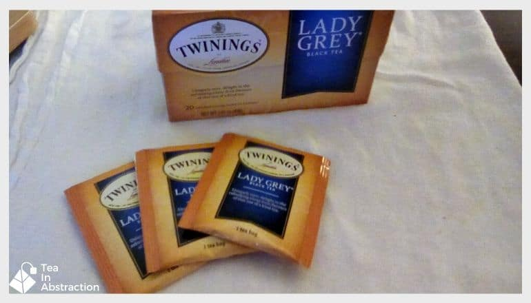 box of lady grey tea and 3 teabags on a white cloth laying on a table