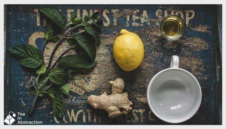 empty tea cup next to a lemon and ginger root on a table with other spices around them