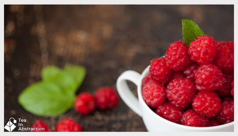 red rspberries in a white cup next to green raspberry leaves