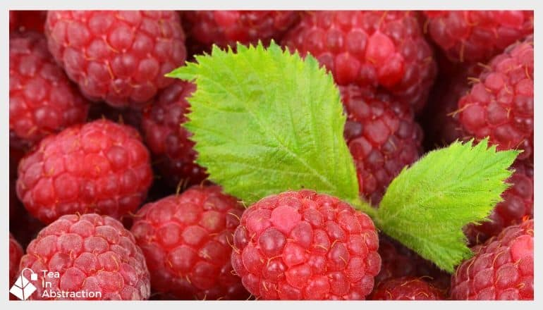 cluster of red rasperries with a green raspberry leaf in the middle