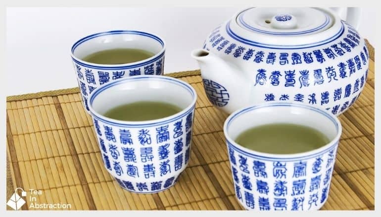 3 cups of green tea in decorative tea cups next to a tea kettle. white with blue writing on them