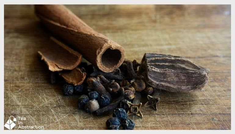 Cardamom, Cinnamon, Cloves And Black Pepper on a wooden table