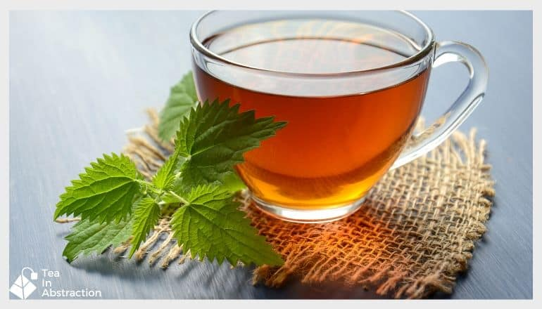 cup of black tea in a clear cup with a piece of fresh mint leaf sitting next to it