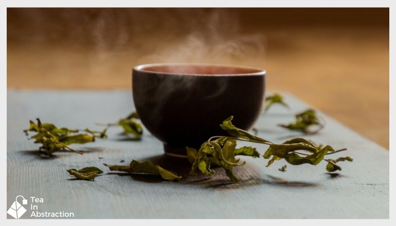 cup of green tea with green tea leaves scattered around the cup