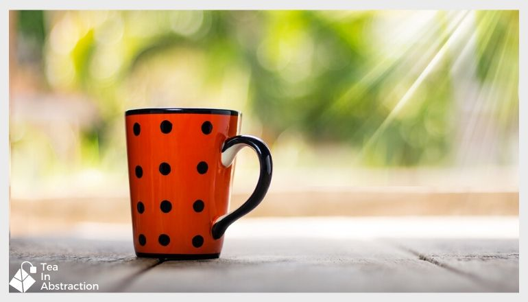 red tea cup with black dots sitting in front of a window