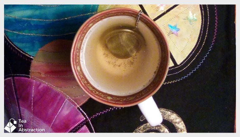 cup of thyme tea with an infuser resting in the water
