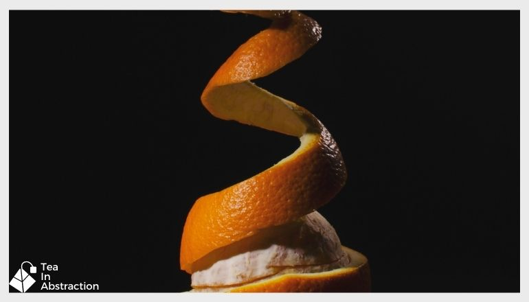 orange peel being pulled off of an orange in a corkscrew fashion